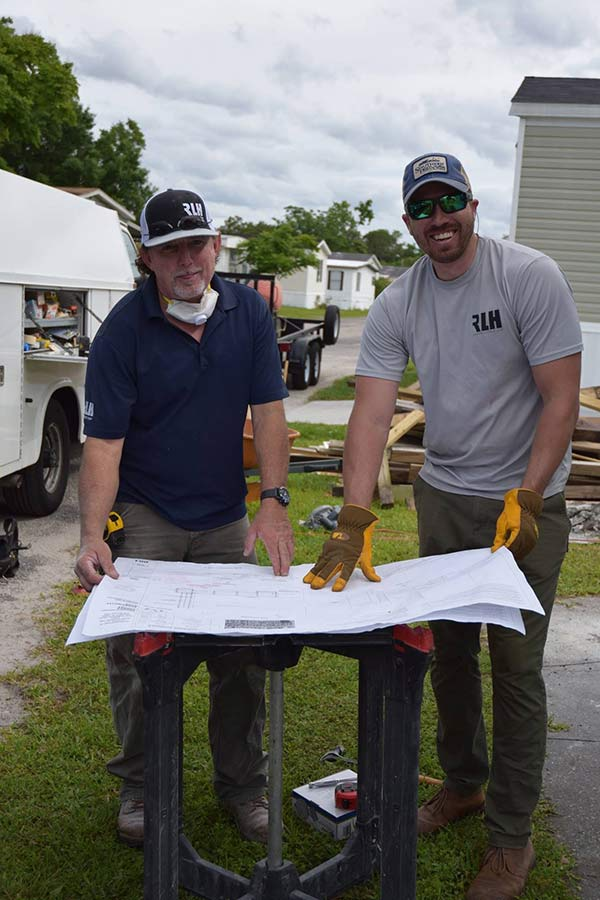 Two guys checking the plans to build the ramp